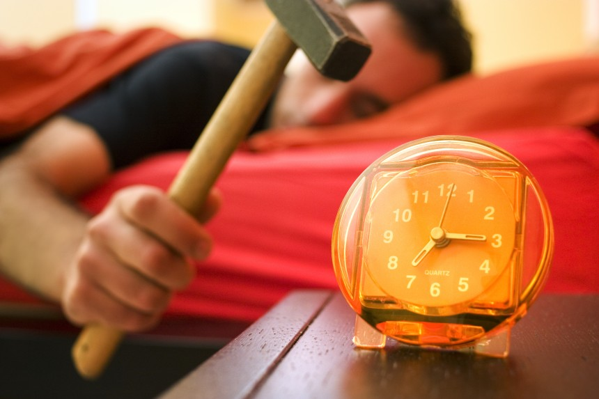 Argh! You want a new job, but what if you don't like it? Man in bed about to use hammer to stop alarm clock