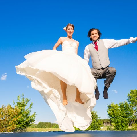 Bride and groom bouncing on a trampoline
